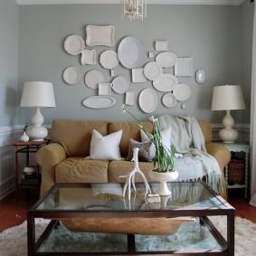 Белые тарелки на серой стене