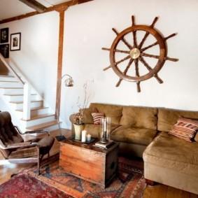 Штурвал старинного корабля над диваном в гостиной