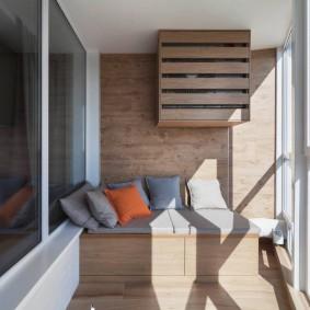 Небольшой диванчик на балконе с окнами до пола