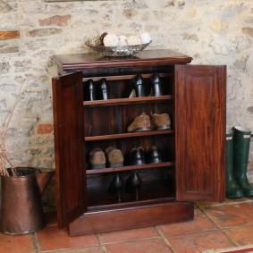 Обувница-тумба около старой кирпичной стены