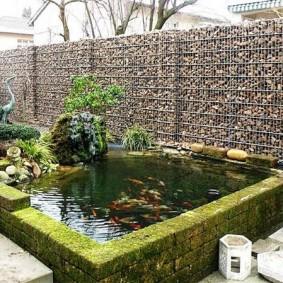 Искусственный водоем около ограды из габионов