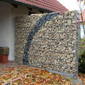 Осенние листья перед стенкой из габионов