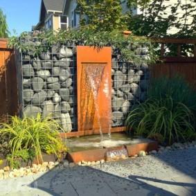 Садовый фонтан в виде высокой стенки из камня