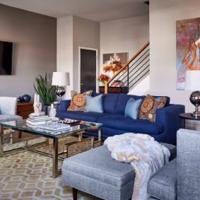 Синий диван в зале загородного дома с лестницей
