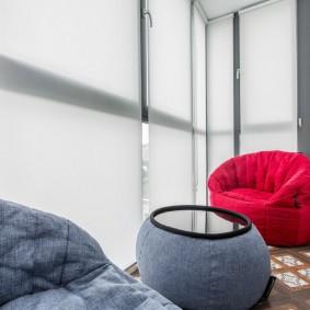Красное кресло на балконе с рулонными шторами