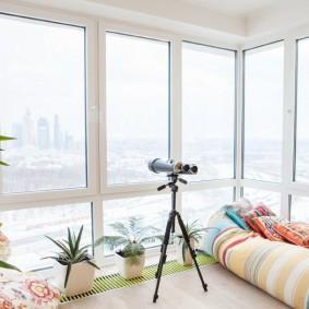 Домашний телескоп на треноге возле окна балкона