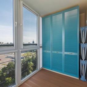 Голубые дверцы шкафа для хранения вещей на лоджии
