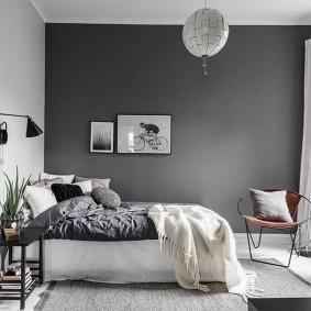 Серая стена в комнате с широкой кроватью
