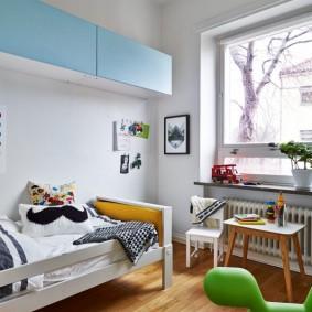 Голубые шкафчики над детской кроватью