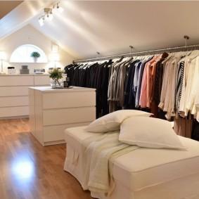 Белый комод по центру гардеробной в мансарде