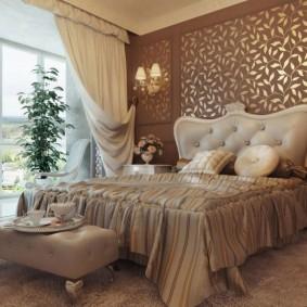 Красивая кровать в спальне с большим окном