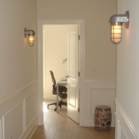 Промышленные светильники на белой стене коридора