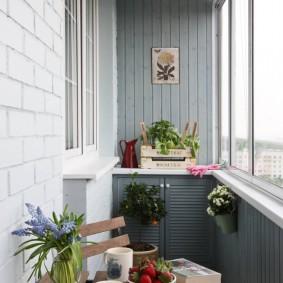 Деревянный столик на лоджии с серыми стенами