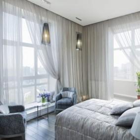 Светлые занавески в угловой спальне