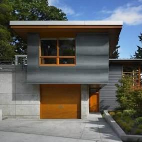 Серый сайдинг на фасаде дома с гаражом