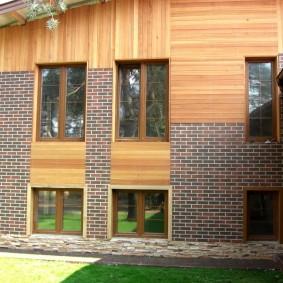 Комбинация цокольного фасада с деревянными панелями