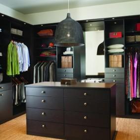 Черный комод посередине гардеробной комнаты