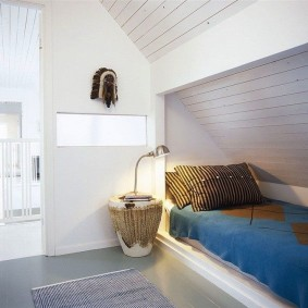Узкая кровать в углублении стены комнаты в мансарде