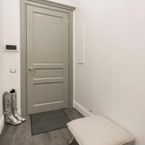 Серая дверь в прихожей с белыми стенами