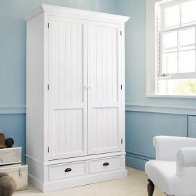 Белый шкаф на фоне голубой стены