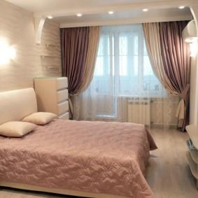 Розовое одеяло на кровати в небольшой спальне