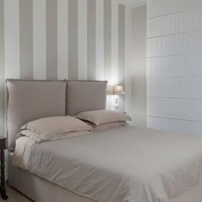 Полосатые обои за спинкой кровати