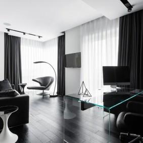 Стеклянный стол в комнате с черным ламинатом
