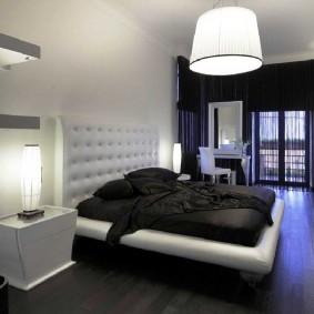 Мягкое изголовье кровати в спальне с черным полом