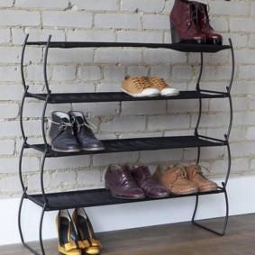 Узкая металлическая обувница у кирпичной стены