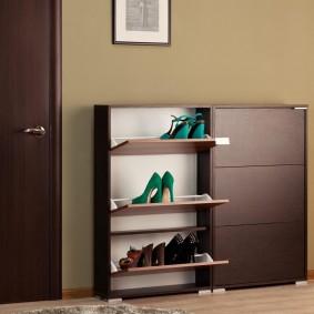 Коричневая обувница у стены в прихожей