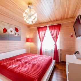 Красные шторы в спальне с деревянной отделкой