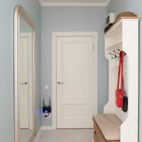 Белая вешалка в коридоре с голубыми стенами