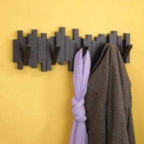 Черная вешалка на желтой стене