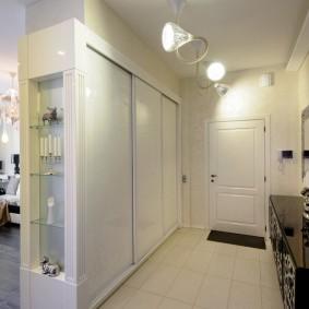 Белый шкаф вдоль стены в коридоре