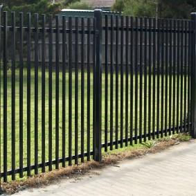 Недорогой забор с вертикальными элементами из профильных труб