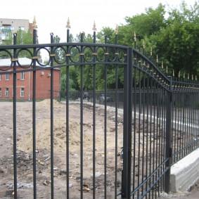 Стальной забор на загородном участке с рельефом