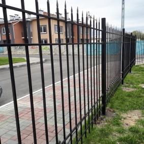 Металлический забор вдоль тротуара с плиткой