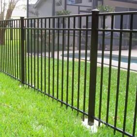 Зеленый газон перед металлическим забором