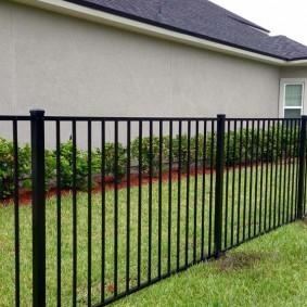 Простой забор перед домом с оштукатуренными стенами