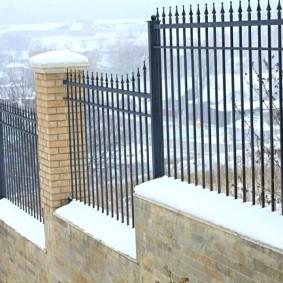 Высокий забор на загородном участке с перепадами высот