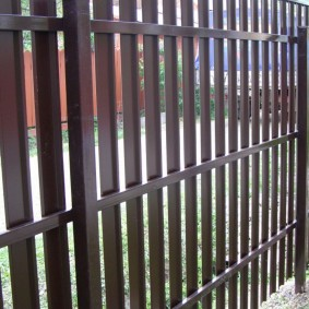 Столбы из профильной трубы на заборе из евроштакетника