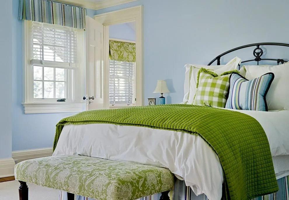Зеленое одеяло на кровати в голубой спальне