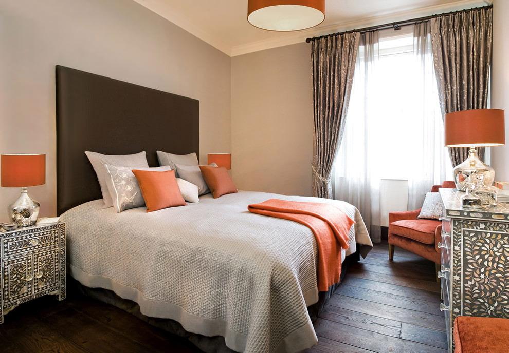 Оранжевые акценты в спальне с коричневым ламинатом