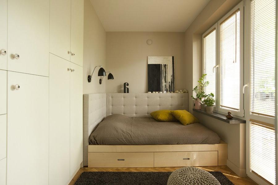 Узкая спальная комната с кроватью подиумом
