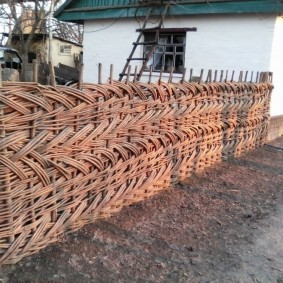 Плетенный забор перед деревенским домом