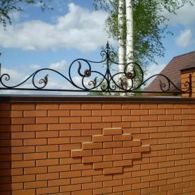 Красивый декор из металла на кирпичном заборе