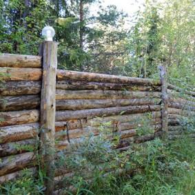 Прочный забор из толстых бревен