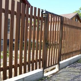 Забор из деревянного штакетника перед сельским домом