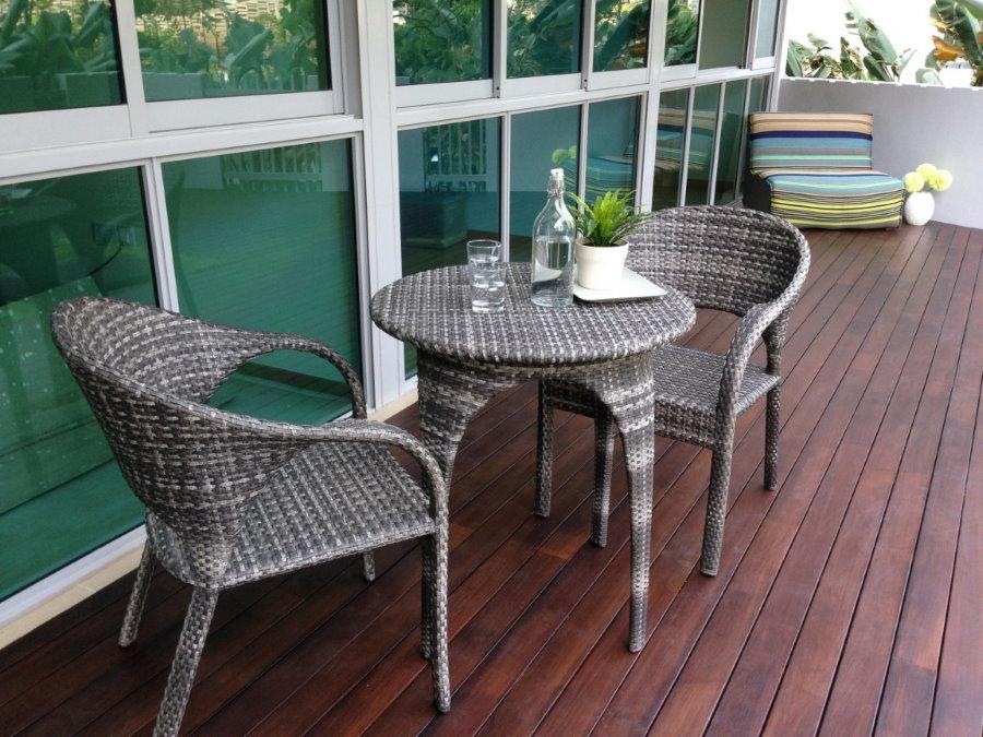 Столик из ротанга на балконе с деревянным полом