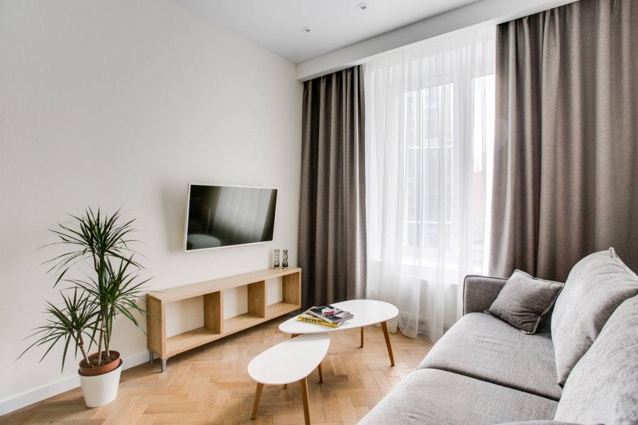 Минимум мебели в гостевой комнате с паркетом на полу